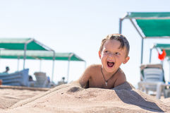 Portrait smiling little baby boy playing in the sand near the sea, ocean. Positive human emotions, feelings, Royalty Free Stock Photos
