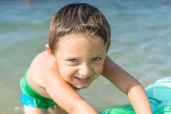 Portrait smiling little baby boy playing in the sea, ocean. Positive human emotions, feelings, joy. Funny cute child making vacati Royalty Free Stock Image