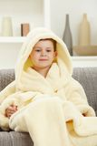 Portrait of smiling little boy in bathrobe at home Stock Image