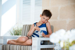 Portrait of smiling little boy eating delicious yogurt Royalty Free Stock Photo