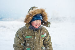 Portrait of a smiling little boy with falling snow Stock Images
