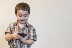 Portrait of a smiling little boy holding mobile phone isolated over light background. cute kid playing games on smartphone. copy. Space stock images