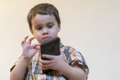 Portrait of a smiling little boy holding mobile phone isolated over light background. cute kid playing games on stock photo