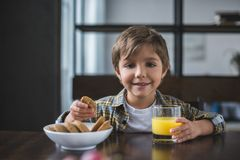Portrait of smiling little boy looking at camera during breakfast. At home stock photo