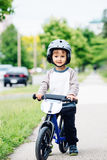 Portrait of smiling little boy toddler riding a balance bike bicycle in helmet on the road outside outdoors on spring summer day Stock Photos