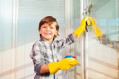 Little boy washing windows using spray bottle Royalty Free Stock Image