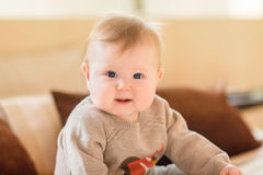 Portrait of smiling little child with blond hair and blue eyes wearing knitted sweater sitting on sofa and looking at camera. Happy childhood royalty free stock photography