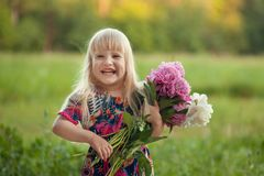 Portrait of a smiling little girl with a bouquet of peonies stock image