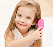 Portrait of smiling little girl brushing her hair Stock Photography