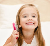 Portrait of smiling little girl brushing her hair Stock Images