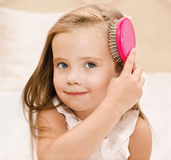 Portrait of smiling little girl brushing her hair Royalty Free Stock Image