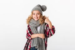 Portrait of a smiling little girl dressed in winter hat. And scarf showing thumbs up over white background royalty free stock images