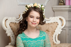 Portrait of a smiling little girl in the flower wreath sitting o stock photos