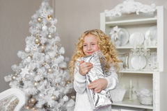 Portrait of smiling little girl with a gift box at hands in a new year decoration studio Royalty Free Stock Photos