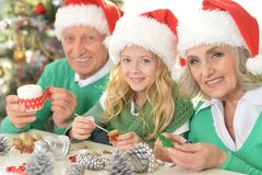 Girl with grandparents preparing for Christmas. Portrait of smiling little girl with grandparents preparing for Christmas Stock Images