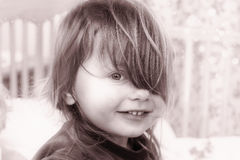 Portrait of a smiling little girl with hair on her left eye Royalty Free Stock Image