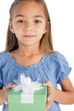 Portrait of a smiling little girl holding a wrapped gift Royalty Free Stock Photography