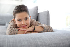 Portrait of smiling little girl lying on couch Royalty Free Stock Images