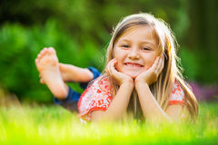 Portrait of a smiling little girl lying on green grass Stock Image