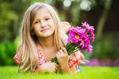 Portrait of a smiling little girl lying on green grass Royalty Free Stock Photo