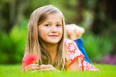 Portrait of a smiling little girl lying on green grass Royalty Free Stock Photography