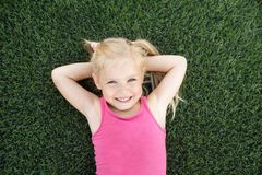 Portrait of a smiling little girl lying on green grass stock images
