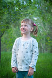 Portrait of smiling little girl in a park amidst green grass Stock Photography