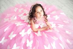 Portrait of smiling little girl in princess pink dress with butterflies stock photography