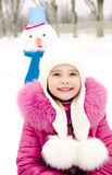 Portrait of smiling little girl with snowman. In winter day outdoor Royalty Free Stock Photo