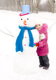 Portrait of smiling little girl with snowman Royalty Free Stock Photos