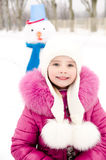 Portrait of smiling little girl with snowman in winter day Stock Photography