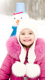 Portrait of smiling little girl with snowman in winter day Royalty Free Stock Photos