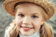 Portrait of smiling little girl in straw hat looking. At camera stock photography