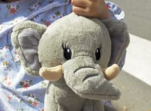 Portrait of smiling little girl with a teddy elephant. royalty free stock photo