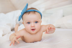 Portrait of smiling little infant with a blue diadem plays on a bed. Portrait of smiling little infant with a blue diadem plays on bed Stock Image