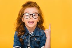 portrait of smiling little kid in eyeglasses pointing up stock image