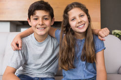 Portrait of smiling little siblings in living room Stock Photo
