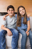 Portrait of smiling little siblings sitting in living room Stock Image