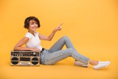 Portrait of a smiling lovely girl sitting with record player. And pointing finger away isolated over yellow background royalty free stock photo