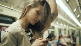 Portrait of a smiling lovely girl typing message on mobile phone in subway train, sexy student blonde woman with. Portrait of a smiling lovely girl typing stock video footage
