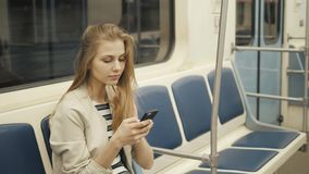 Portrait of a smiling lovely girl typing message on mobile phone in subway train, sexy student blonde woman with stock video footage