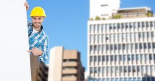 Portrait of smiling male architect pointing at blank billboard against buildings Royalty Free Stock Image