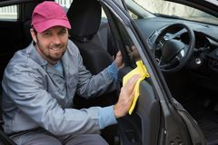 Male auto service staff cleaning car door. Portrait of smiling male auto service staff cleaning car door Royalty Free Stock Images