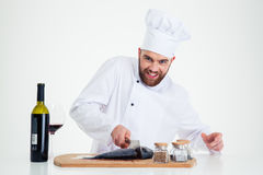 Portrait of a smiling male chef cook cutting fish Stock Photos