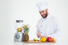 Portrait of a smiling male chef cook cutting fruits Royalty Free Stock Images