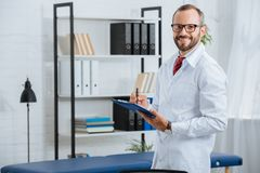 portrait of smiling male chiropractor in white coat and eyeglasses with notepad