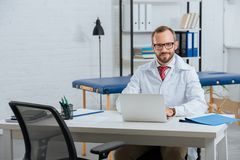 portrait of smiling male chiropractor in white coat at workplace with laptop