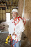 Portrait of a smiling male construction worker holding a power saw and a red electric wire Royalty Free Stock Photo