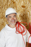 Portrait of smiling male construction worker with a red electrical wire Stock Photo