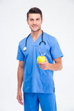 Portrait of a smiling male doctor holding apple i Stock Image